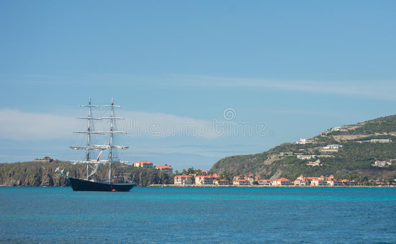 Sail boat in Caribbean waters near mountainous island royalty free stock photos