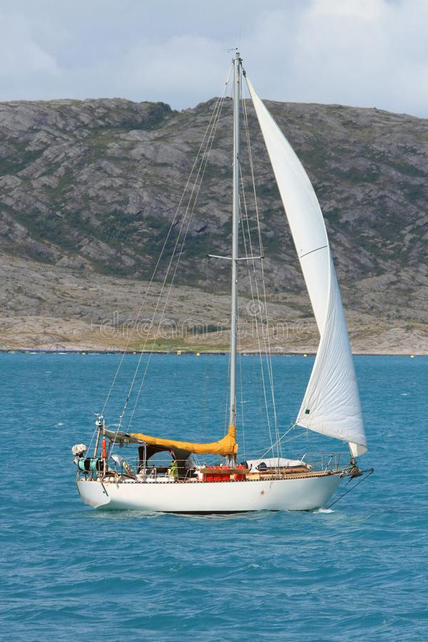 Sail boat facing the salmon farm of Fleina. Island of Nordland County Arctic Norway stock photos