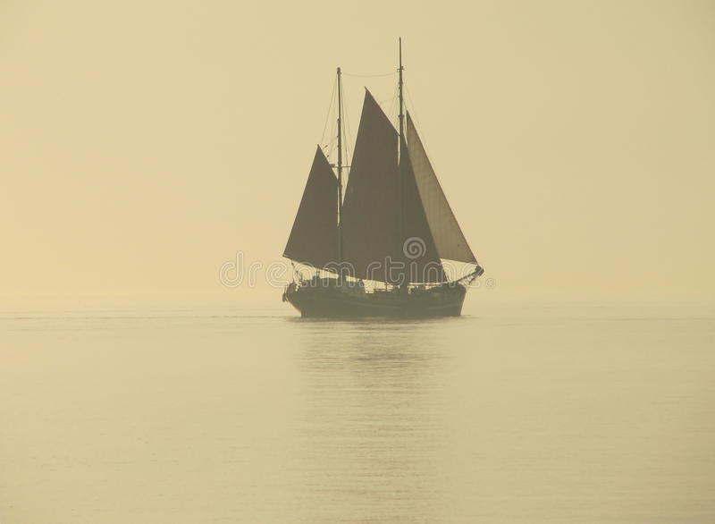 Sail boat in fog royalty free stock photo