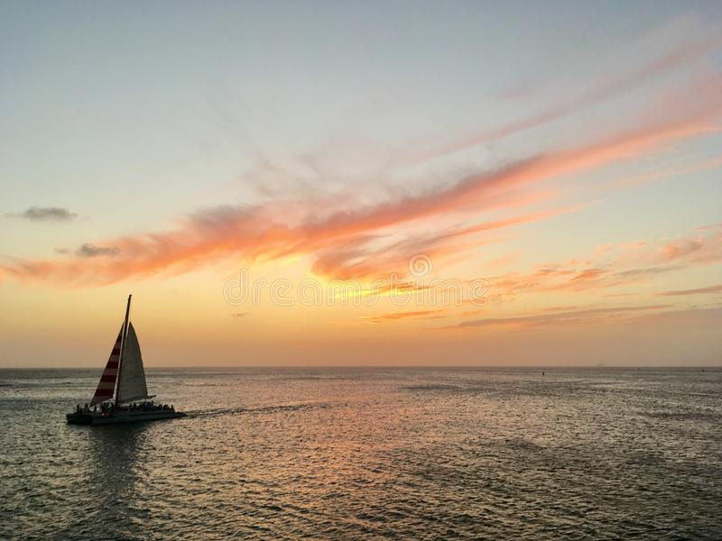Sail boat at sea during sunrise royalty free stock images