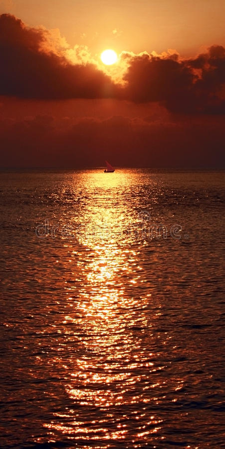 Sail Boat silhouetted in glittering setting sun on the Indian Ocean stock images
