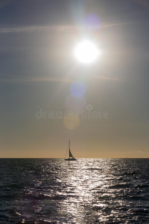Sail boat silhouetted in the setting sun over the ocean in Mexico royalty free stock photography