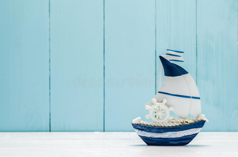 Sail boat Toy model. With Ship`wheel, rope and seashell on white and blue wooden background royalty free stock images