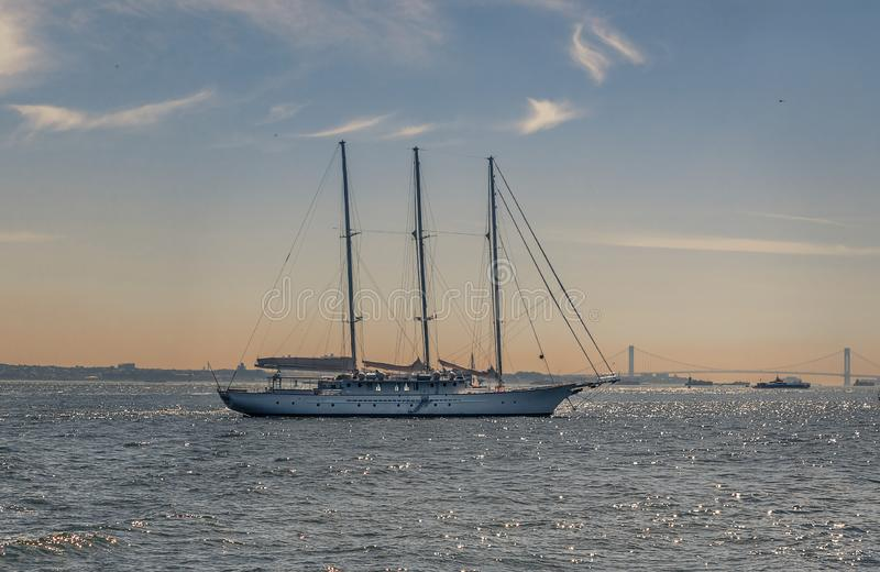 Sail boat traveling in New York's Hudson Bay in front of a bridge during the golden hour of sunet stock photography