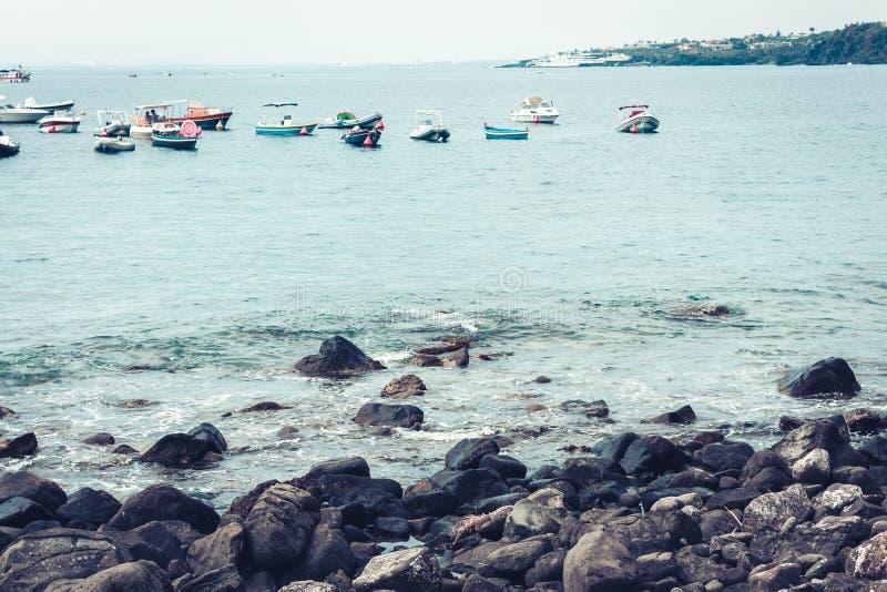 Sail and pleasure boats near Acitrezza harbor next to Cyclops islands, Catania, Sicily.  stock photo