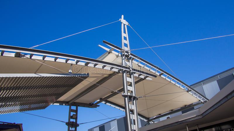 Sail shade pergola made of galvanized steel and stainless steel wire cable tall structure against the blue sky d stock images