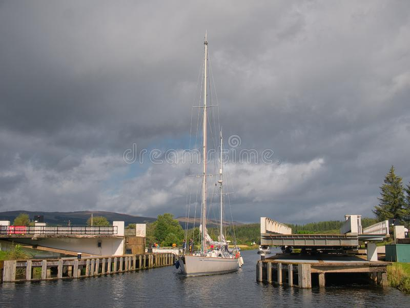 The sail training ketch Ocean Spirit of Moray passes through an open swing bridge on the Caledonian Canal. stock photos