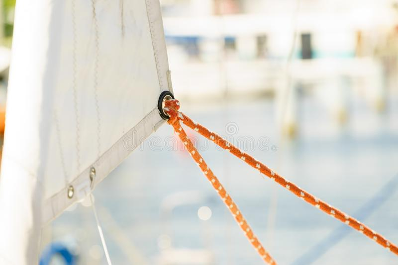Sail wit rope on boat. Yachting. Sailboat view of different parts of yacht, sail with rope. Detail of a sailing boat stock photo