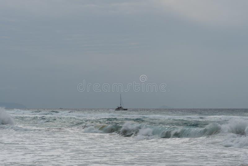 Sailboat από την ακτή Kauai ` s της μακρινής παραλίας στην άκρη της ακτής Napali στοκ εικόνες