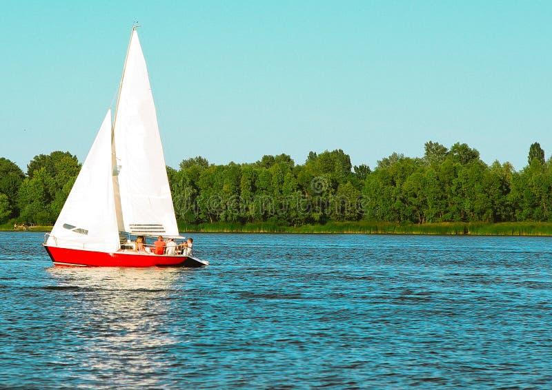 Sailboat γιοτ κινήσεις κατά μήκος του αυξημένου πλήρωμα πανιού νερού στοκ εικόνες
