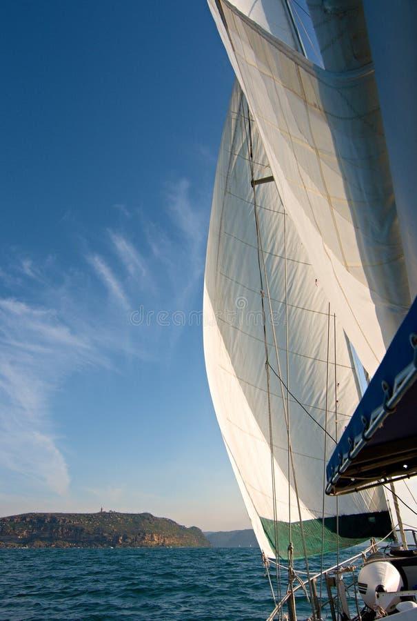 Sailboat εν πλω κάτω από το πλήρες πανί με την προσέγγιση σε ξηρά στην απόσταση στοκ εικόνα με δικαίωμα ελεύθερης χρήσης