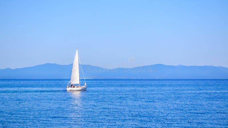 Sailboat κατά τη διάρκεια του διεθνούς regatta ναυσιπλοΐας στο υπόβαθρο του ρωσικού νησιού στοκ φωτογραφίες