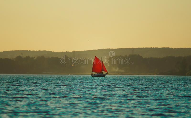 Sailboat με τα κόκκινα πανιά που επιπλέουν στη λίμνη στοκ φωτογραφία