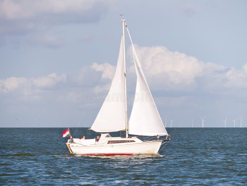 Sailboat που πλέει με τη λίμνη IJsselmeer και τα windturbines του windfarm στοκ φωτογραφία με δικαίωμα ελεύθερης χρήσης