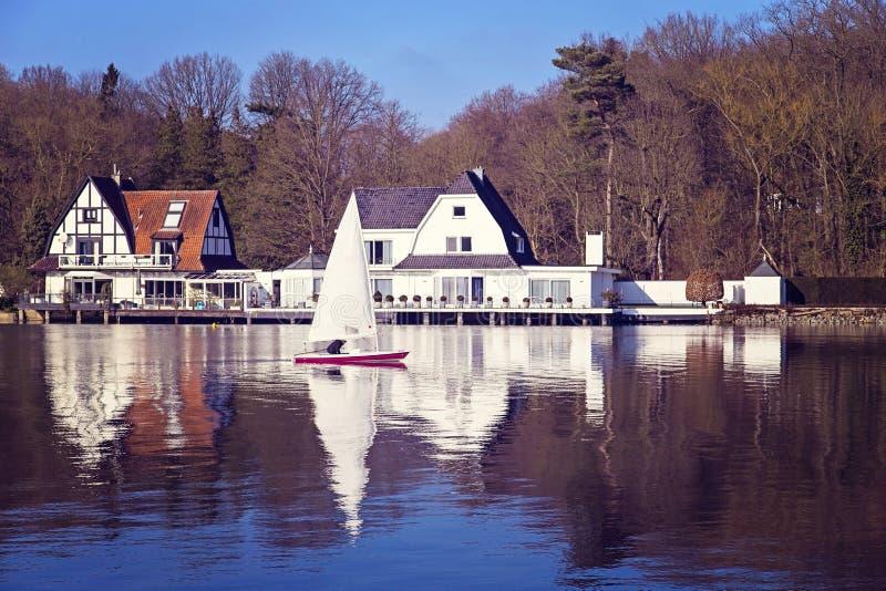 Sailboat τα άσπρα πανιά που απεικονίζονται με στο νερό στο Βέλγιο στοκ φωτογραφία με δικαίωμα ελεύθερης χρήσης