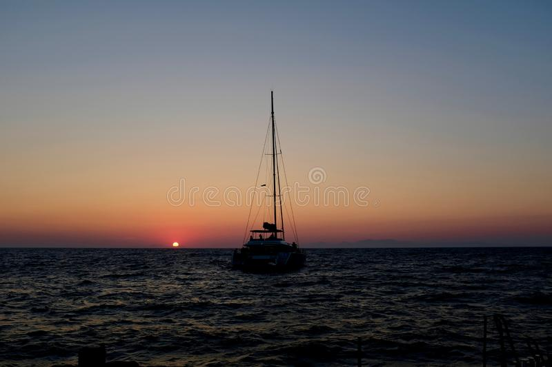 Sailboat in the Aegean Sea at Sunset. Tour sailboat in the Aegean Sea at sunset, in the caldera, Santorini, Greece royalty free stock images