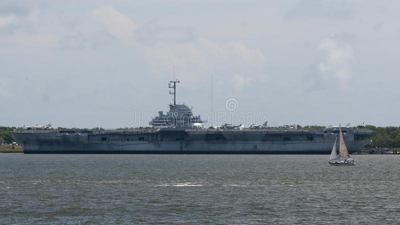 Sailboat along side the USS Yorktown Aircraft Carrier royalty free stock images