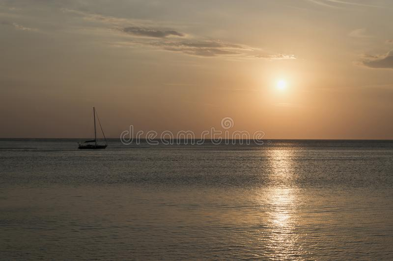 Sailboat anchored in open sea during sunset. Romantic sailing boat yacht sundown photo. stock photos