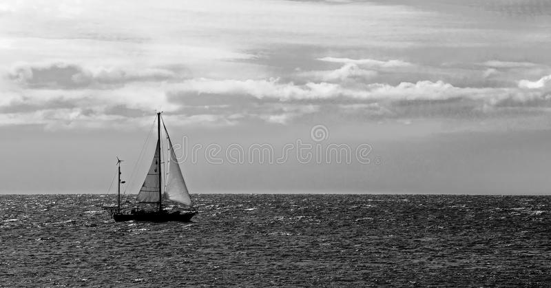 Sailboat on the Atlantic Ocean under a cloudy sky black and white. A sailboat travels across the horizon on the Atlantic Ocean under a cloudy sky stock photography