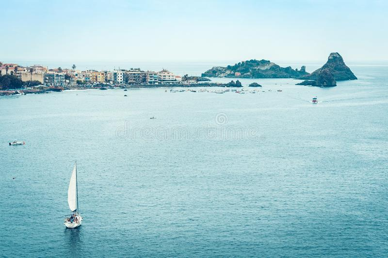 Sailboat on the background of Acitrezza rocks of the Cyclops, sea stacks in Catania, Sicily, Italy stock image