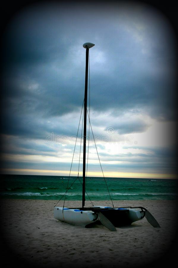Sailboat on the beach in front of rough seas. Stormy, waves stock photo