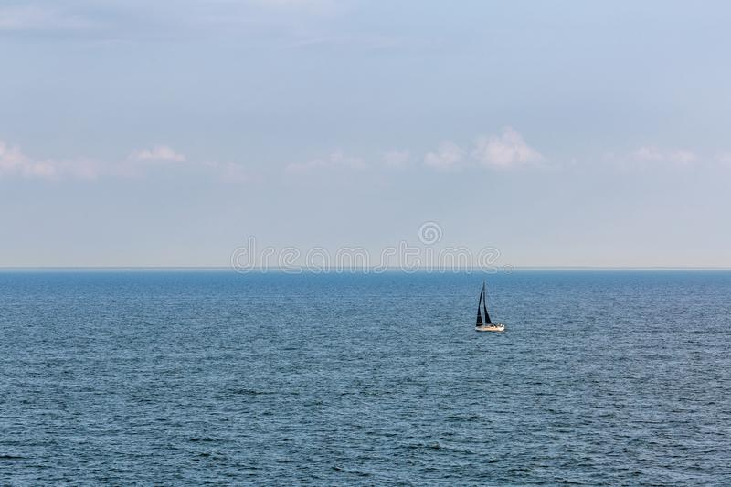 A sailboat with a black sail. In the sea royalty free stock photography