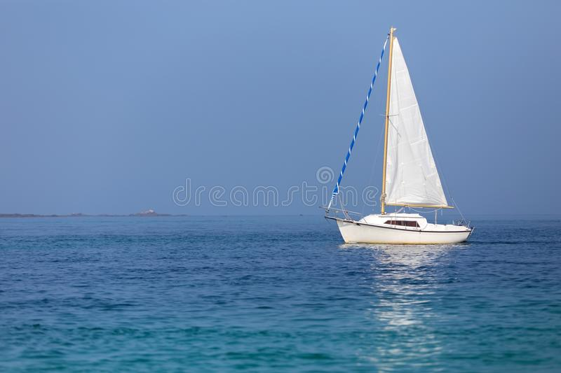 Sailboat on calm sea. Under a sunny summer day royalty free stock photo