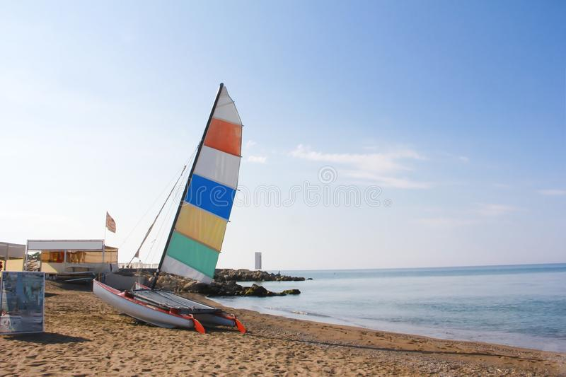 Sailboat catamaran with multi-colored flag on a background of blue sea stock photography
