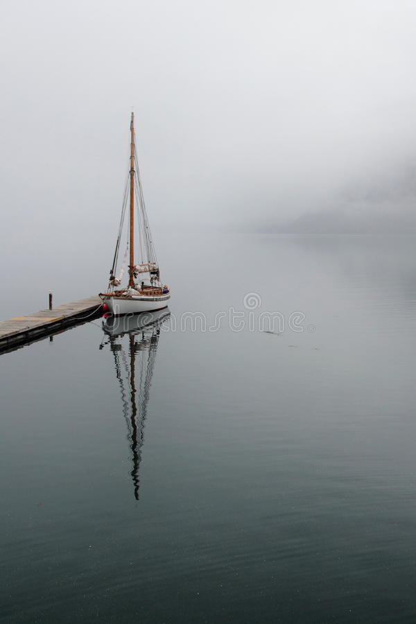 Sailboat and fog. Sailboat mirroring in a foggy Holandsfjord, in front of Svartisen Glacier, the lowest glacier of europe royalty free stock image