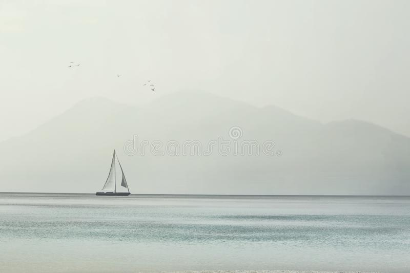 Sailboat glides lightly on the waves of a spectacular ocean royalty free stock photo