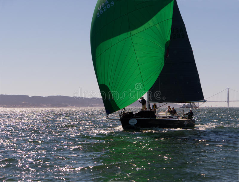 Sailboat with green spinnakers at Rolex Cup. Sailboat flying spinnaker competing at Rolex Cup sailing event in San Francisco September 2015. Golden Gate bridge stock image
