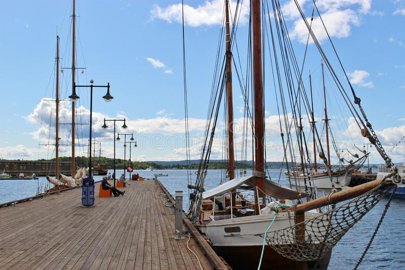 A sailboat in the harbor Pipervika in the center of Oslo, capital of Norway, Europe. People are relaxing on the Pier royalty free stock photo