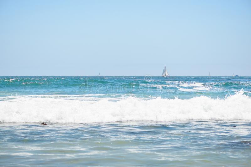 A sailboat on the horizon in the ocean stock photo