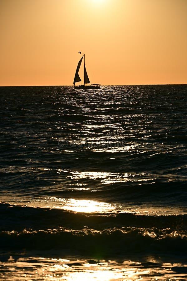 Sailboat on the horizon at sunset stock photos