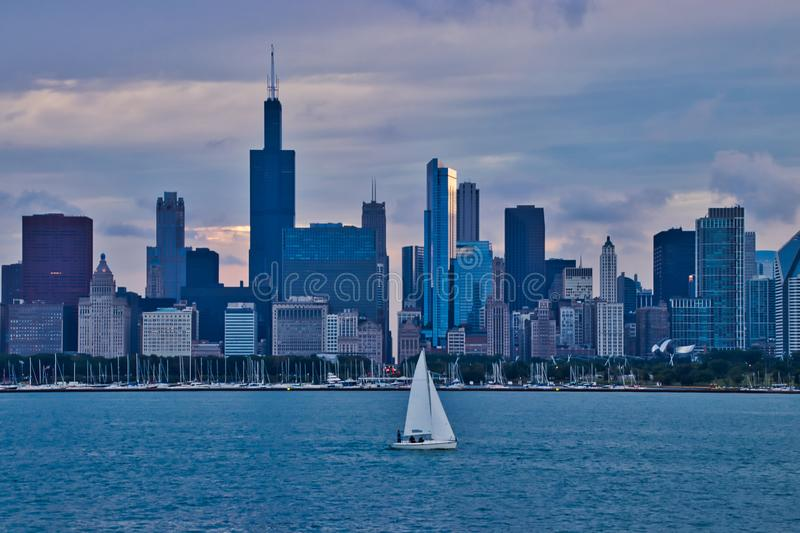 Sailboat on Lake Michigan with Chicago skyline in background as sun begins to set. In summer stock photos