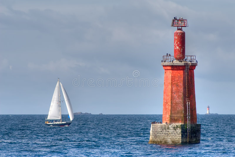Sailboat and lighthouse royalty free stock image