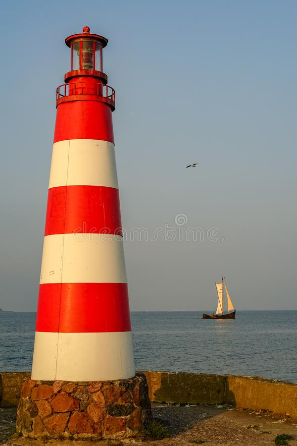 Sailboat and lighthouse fragment at the pier stock photo