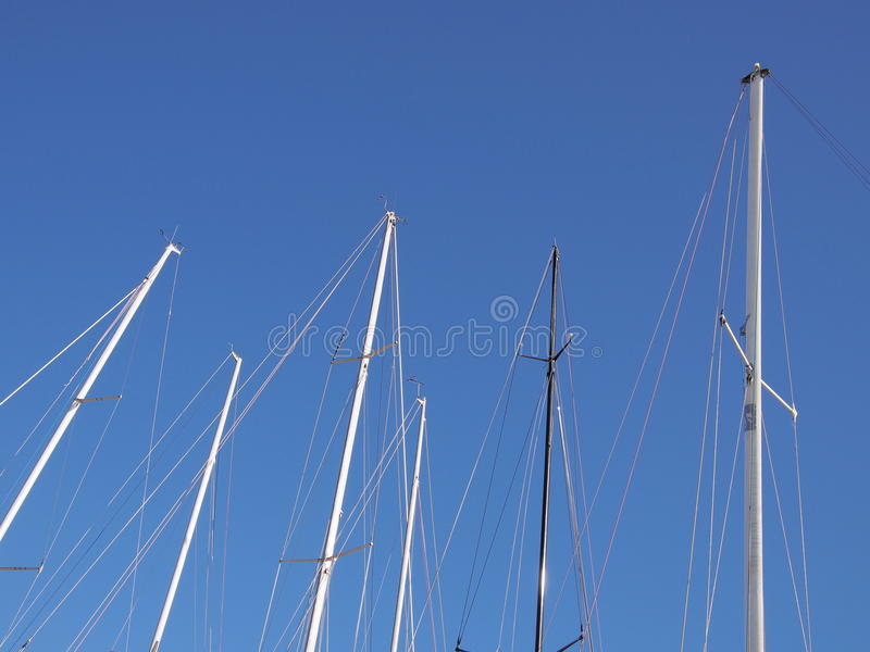 Sailboat masts against the blue sky stock photo