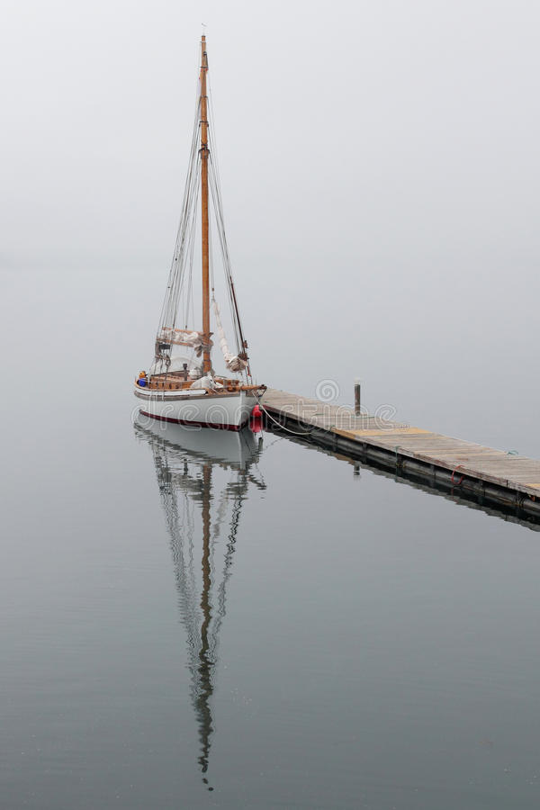 Sailboat mirrors in a foggy Holandsfjord. Sailboat mirroring in a foggy Holandsfjord, in front of Svartisen Glacier, the lowest glacier of europe stock image