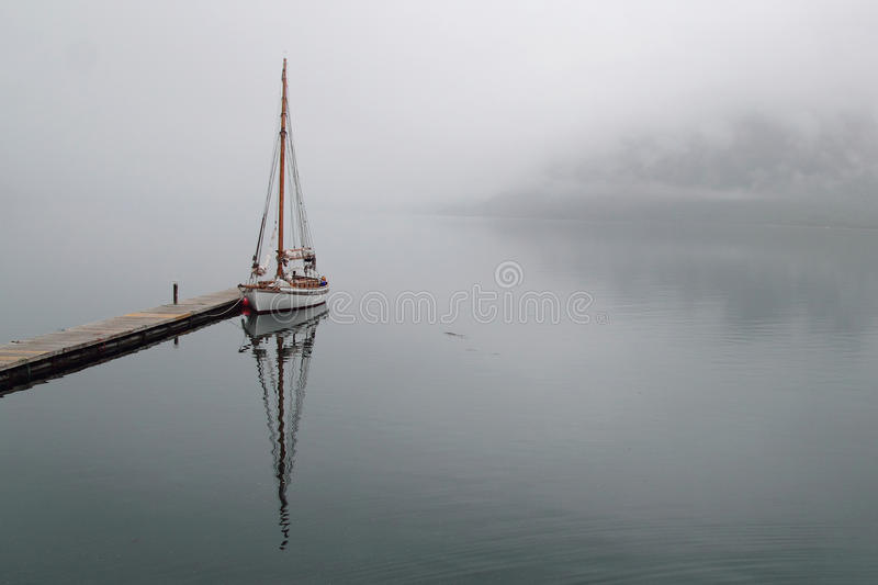 Sailboat mirrors in Holandsfjord. Sailboat mirroring in a foggy Holandsfjord, in front of Svartisen Glacier, the lowest glacier of europe stock photo