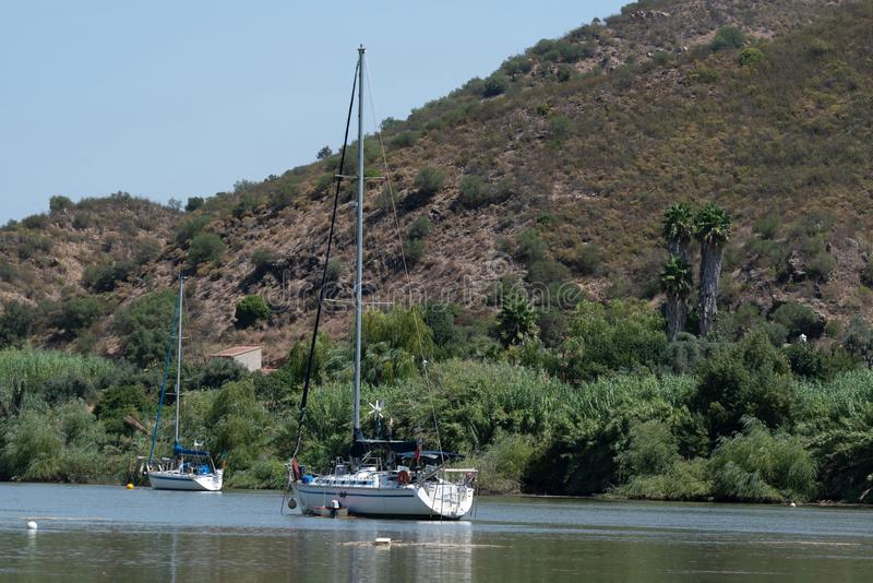 Sailboat and motorboat moored on Rio Guadiana. The human presence in the territory that currently constitutes the municipality of Alcoutim can be traced back stock photo