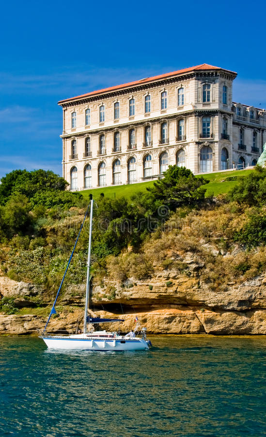 Sailboat passing under cliff. Sailboat passing near Marseille, France royalty free stock photography