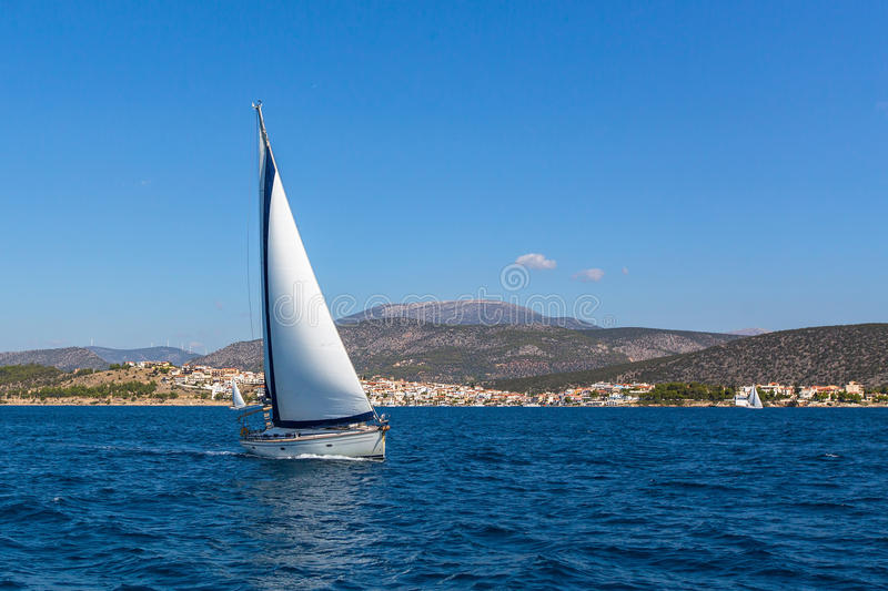 Sailboat on peaceful still waters in a harbor.cruise . royalty free stock photography