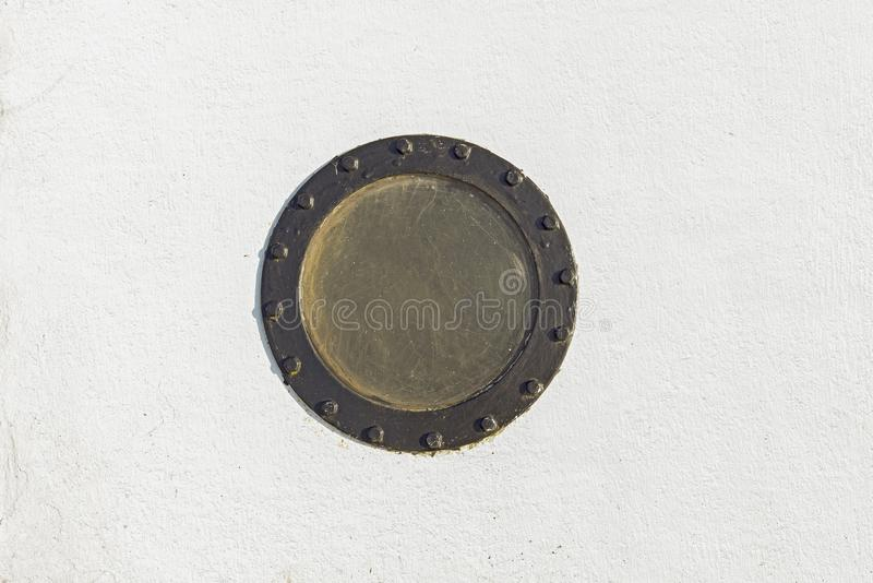 Sailboat porthole in white grunge metal wall. stock images