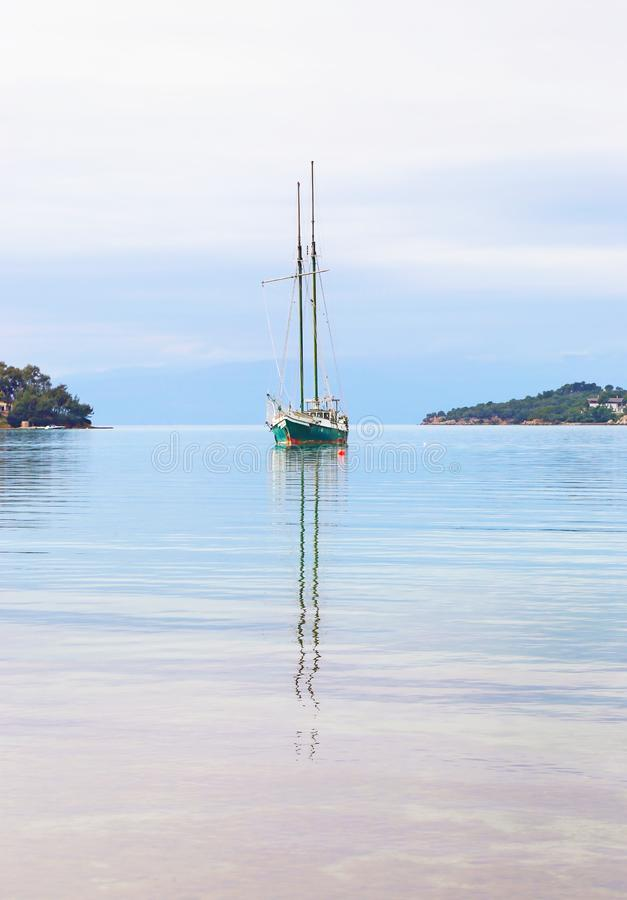 Sailboat reflected on sea at Porto Heli beach Argolis Greece stock photography