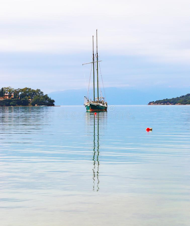 Sailboat reflected on sea at Porto Heli beach Argolis Greece. Greek summer destination stock photo