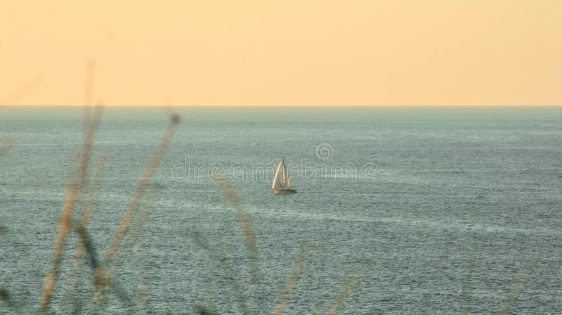 Sailboat sailing through the Cantabrian Sea at sunset. Sailboat sailing in the cantabrian sea at sunset with the horizon line in the background and an orange sky royalty free stock photos