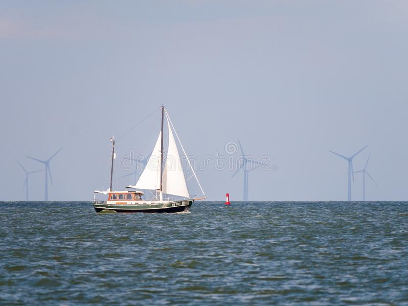Sailboat sailing on lake IJsselmeer and windturbines of windfarm Urk, Netherlands royalty free stock image