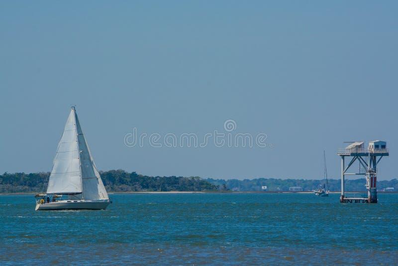 Sailboat sailing past the state line marker on the Cumberland Sound. Fernandina Beach, Nassau County, Florida USA. Sailboat sailing on Cumberland Sound royalty free stock photo