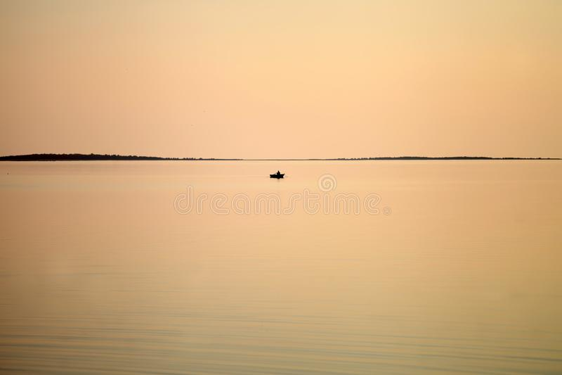 Sailboat in the sea in the evening coral colour sunlight, luxury summer adventure stock image